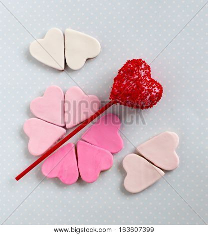 Red cakepop with hearts blue background, sweets