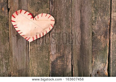 Self-made heart from paper on old boards. Edges of heart are sewed by a red thread boards gray not colored space free on the right