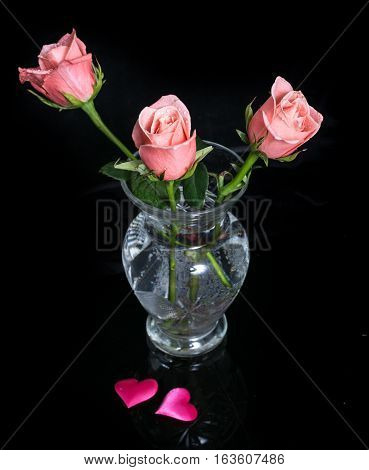 Pink roses in a glass vase and two hearts on black. Three roses and two hearts from pink fabric on a black background