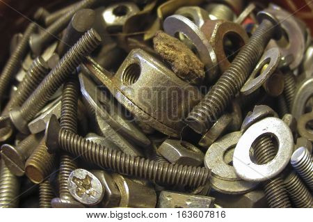 a variety of small screws washers and nuts lying in a container as a background