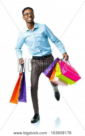 Happy african american man holding shopping bags on white background. Christmas and holidays concept