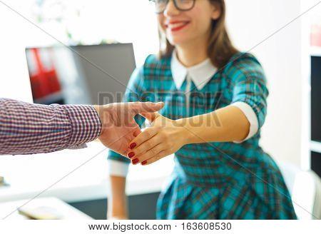 Modern young business woman with arm extended to handshake