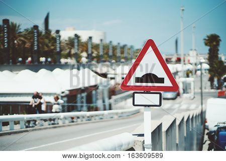 Close-up view of triangular speed bump road sign with blank place for additional information near sloping road on sunny and bright summer day Barcelona Spain
