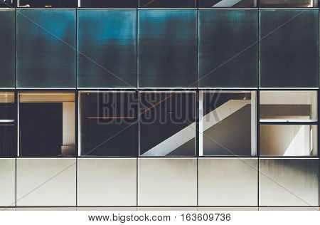 Blue and white modern facade of contemporary building with several rows of metal and glass plates in Barcelona on sunny summer day