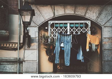 Close up view of facade of historical residential building in Barcelona district El Born with lantern plants and a lot of drying clothes in front of arc window on summer day Spain