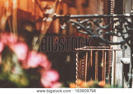 Empty old rusty metal balcony with blurred narrow street behind and lantern with pink flowers in front historical district of Barcelona - El Born on sunny summer day Spain