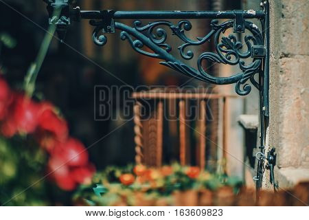 Fragment of base of old black metal toreutic lantern with blurred rusty balcony behind and red flowers in front historical district of Barcelona - El Born on sunny summer day Spain