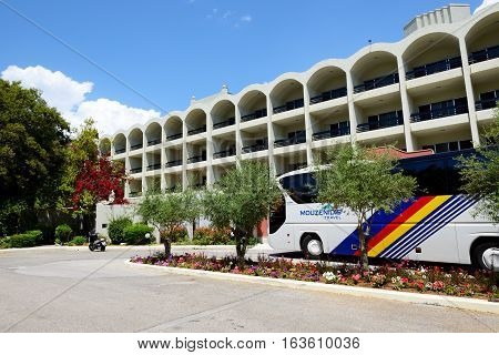 CORFU GREEES - MAY 16: The modern bus for tourists transportation is near entrance to hotel on May 16 2016 in Corfu Greece. Up to 16 mln tourists is expected to visit Greece in year 2016.