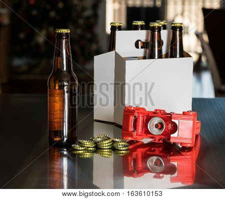 Home brewed beer uses a red bottle capper to attach the metal cap to the top of the glass bottle, with a six pack in background