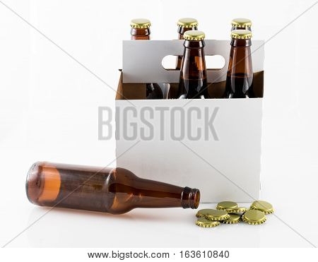 Five beer bottles in cardboard carrier with side of container facing camera and single bottle lying on table with caps