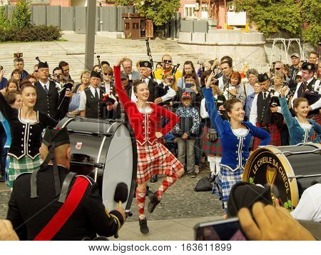 MOSCOW, RUSSIA - September 4, 2016: Girls dancing during show of Celtic pipes and drums band surrounded by townspeople in the Park on the Crimean embankment. Festival of military orchestras