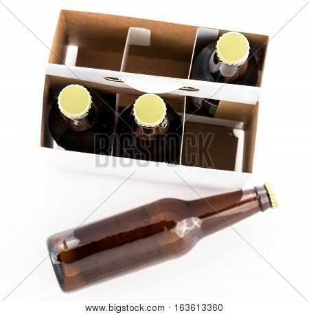 Pattern of three beer bottles in six pack cardboard container with gold caps facing upwards, with a fourth bottle laying on the table top