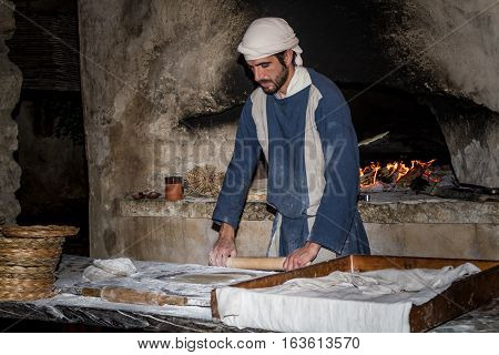 NAZARETH ISRAEL - DECEMBER 16: Man dressed in period clothes rolls the dough with rolling pin in Nazareth Village Israel on December 16 2016