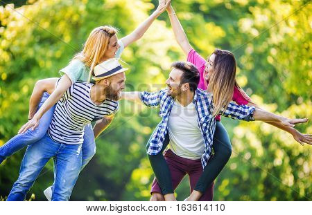 Friends having fun in park.Young cheerful people piggybacking in the park during springtime.