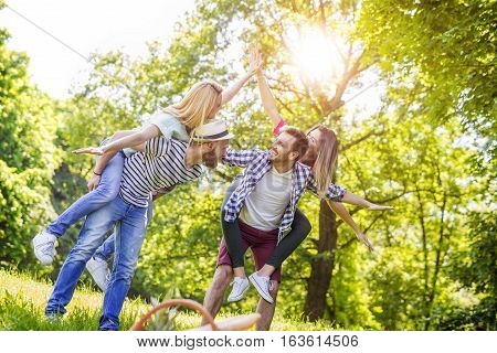 Friends having fun in the park.Young cheerful people piggybacking in the park during springtime.