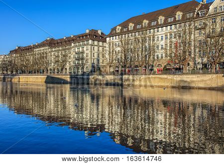 Zurich, Switzerland - 1 January, 2017: the Limmat river, trees and buildings along it in wintertime. The Limmat is a river, which commences at the outfall of Lake Zurich in the southern part of the city of Zurich and flows in northwesterly direction.