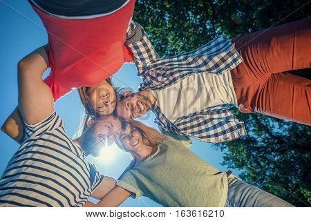 Happy group of friends hugging at the park