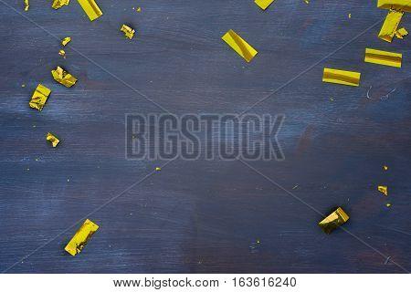 Carnaval golden confetti decorations on dark wooden background