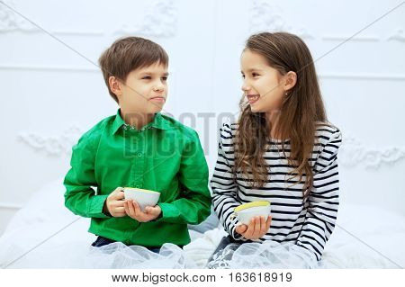Small children talking and drinking tea. The concept of love and Valentine's Day.