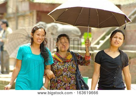 Three Women Walk In Durbar Square And Protect Form The Sun With An Umbrella.