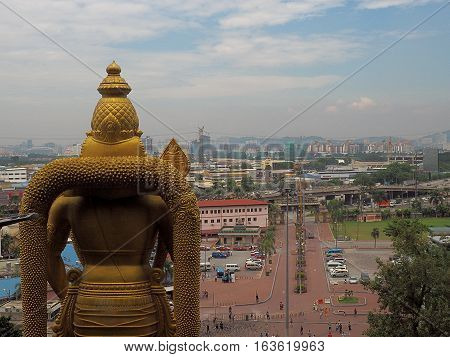 Lord Muruga and the panorama of the city .. Batu, Malaysia - June 01, 2016 The statue of Lord Muruga of Cave Batu Caves on the background panorama of Kuala Lampur, Malaysia's capital.