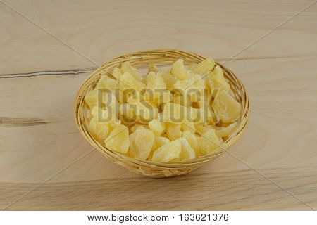 Dried pineapple pieces in wooden basket on wooden table