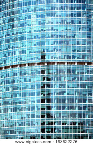 Glass wall of modern office building with many large panoramic windows in business cluster vertical front view close-up