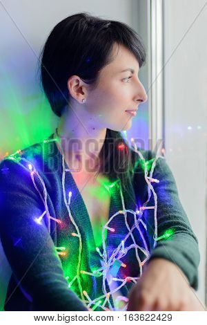 young woman entwined colorful festive garland sitting on window sill