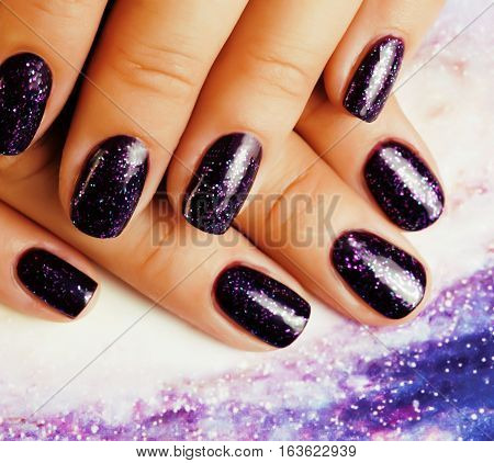 manicure stylish concept: woman fingers with nails purple glitter on nails like cosmos, universe background close up