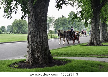 Quebec City Canada - June 13 2010: Horses and carriages make their way through park in Quebec City
