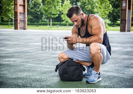 Attractive muscleman using cell phone from his bag in city park, ready for training or jogging