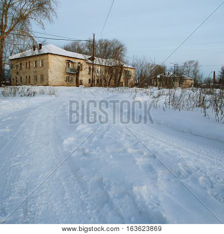 View of the winter road and old two story house