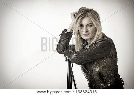 Portrait of an attractive woman in torn jeans sitting in chair against white studio background
