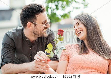 Man surprising his girlfriend with a red rose.