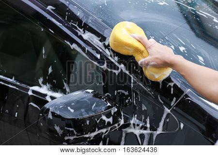Washing car.Female hand with yellow sponge washing car