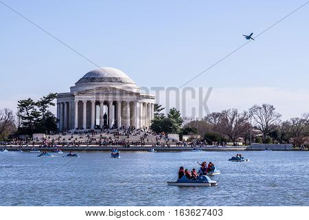 WASHINGTON, D.C. - APRIL 6, 2014: People having fun in paddle boats in the tidal basin, with the Jefferson Memorial and an airplane taking off in the background.