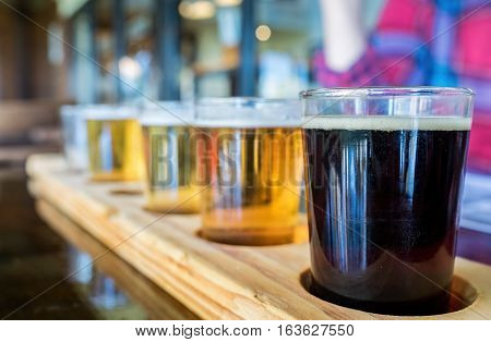 Beer samplers in small glasses individually placed in holes fashioned into a unique wooden tray. Focus is on the backlit front dark stout.