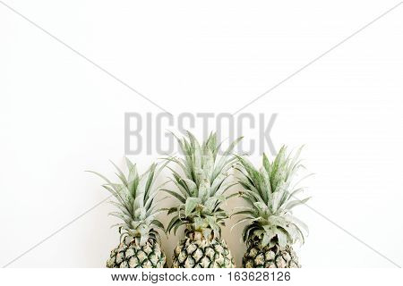 Three pineapples on white. Flat lay top view