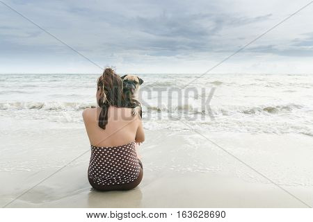 Sad woman sit on white sand beach on the sea and carry cute pug dog for soothe with dark cloudy
