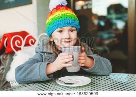 Adorable little 6 year old girl drinking hot chocolate in winter cafe, holding big cup, wearing grey coat and colorful hat