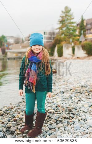 Outdoor portrait of adorable 7 year old little girl, standing by the lake, wearing warm green jacket and blue hat