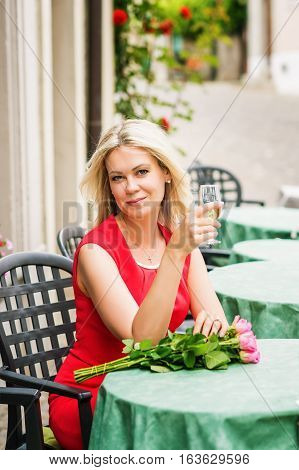 Outdoor portrait of beautiful blond woman holding bouquet of pink roses, resting in cafe, holding glass of white wine