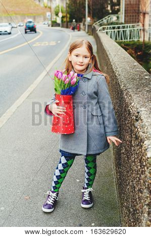 Spring portrait of 7 year old girl holding polka dot watering can with fresh pink tulips, wearing grey coat, green tights and purple shoes