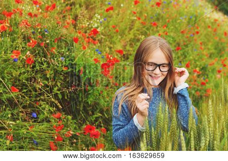 Outdoor portrait of adorable little blond girl of 8-9 years old in poppy field, wearing eyeglasses