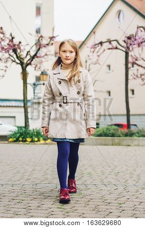 Little girl walking down the street, wearing beige coat, blue tights and red shoes