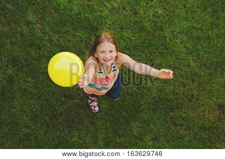 Happy little girl of 8-9 years old playing with white balloon outdoors, top view