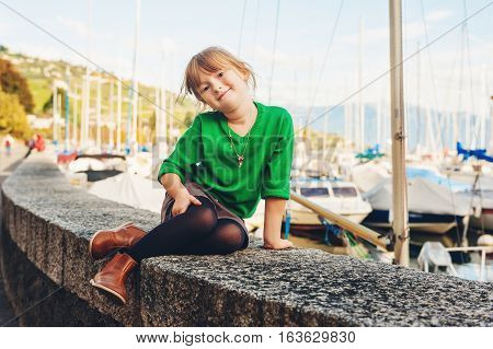 Fashion portrait of adorable 5 year old little girl resting by the lake