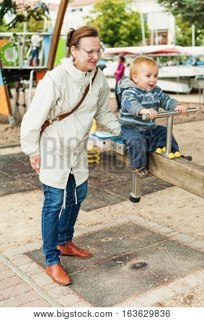 Little baby boy having fun on playground. Grandmother spending time with grandson