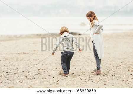 Two little kids playing outdoors by the lake, wearing grey clothes