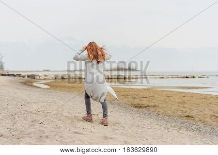 Adorable little girl of 8-9 years old playing by the lake, wearing grey trousers and long cardigan, back view